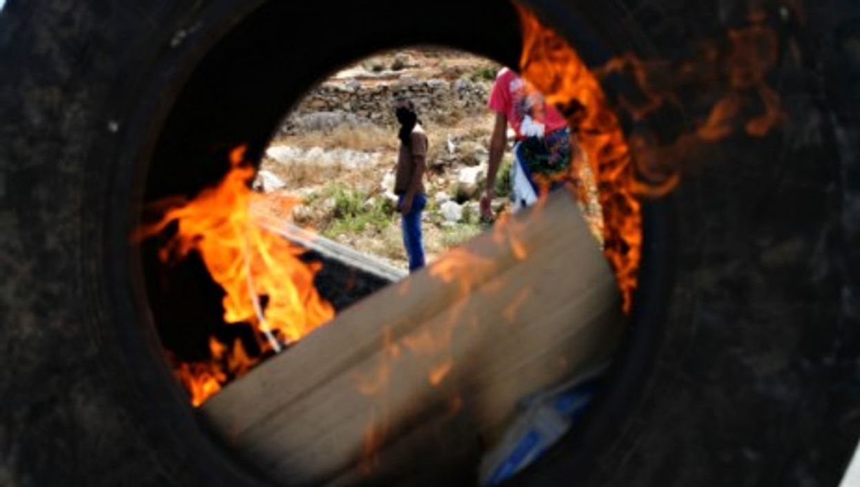Palestinian protesters burning tires in Ramallah, West Bank, in solidarity with Gaza