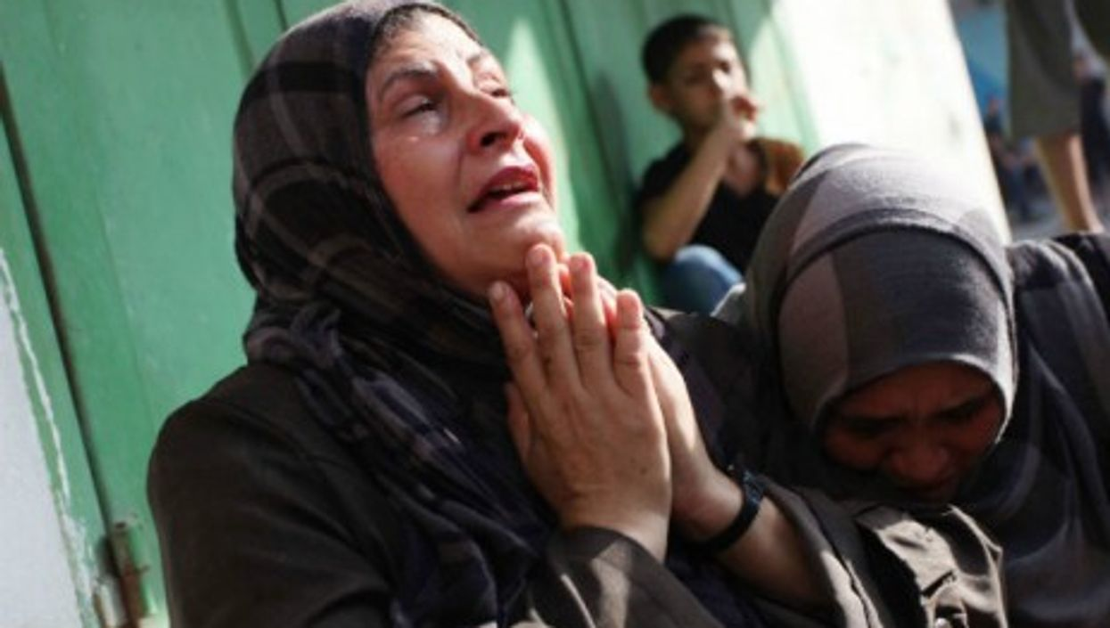 Palestinian relatives of victims after Israeli air strikes hit a refugee camp in Gaza