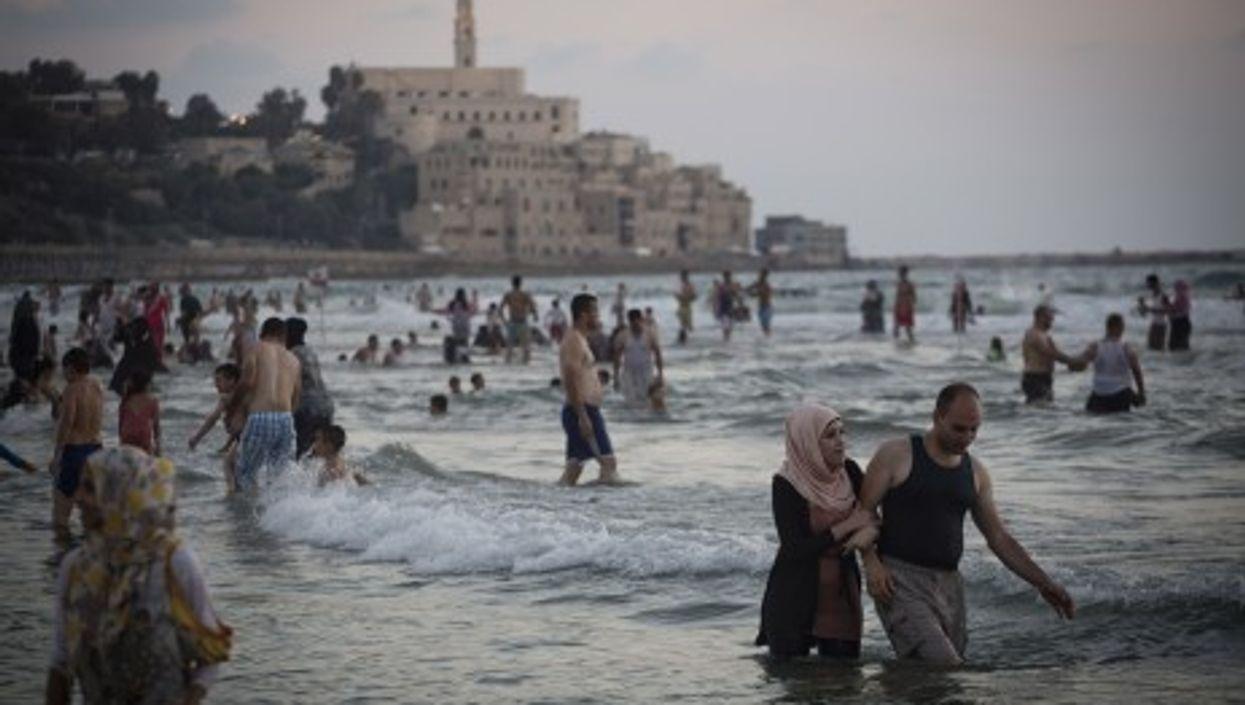 Palestinians from the West Bank enjoy the Mediterranean Sea during Ramadan, Tel Aviv, Aug. 11, 2013.