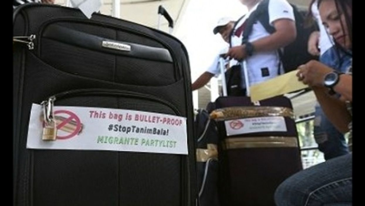 Passengers at Manila airport with anti-scam stickers.