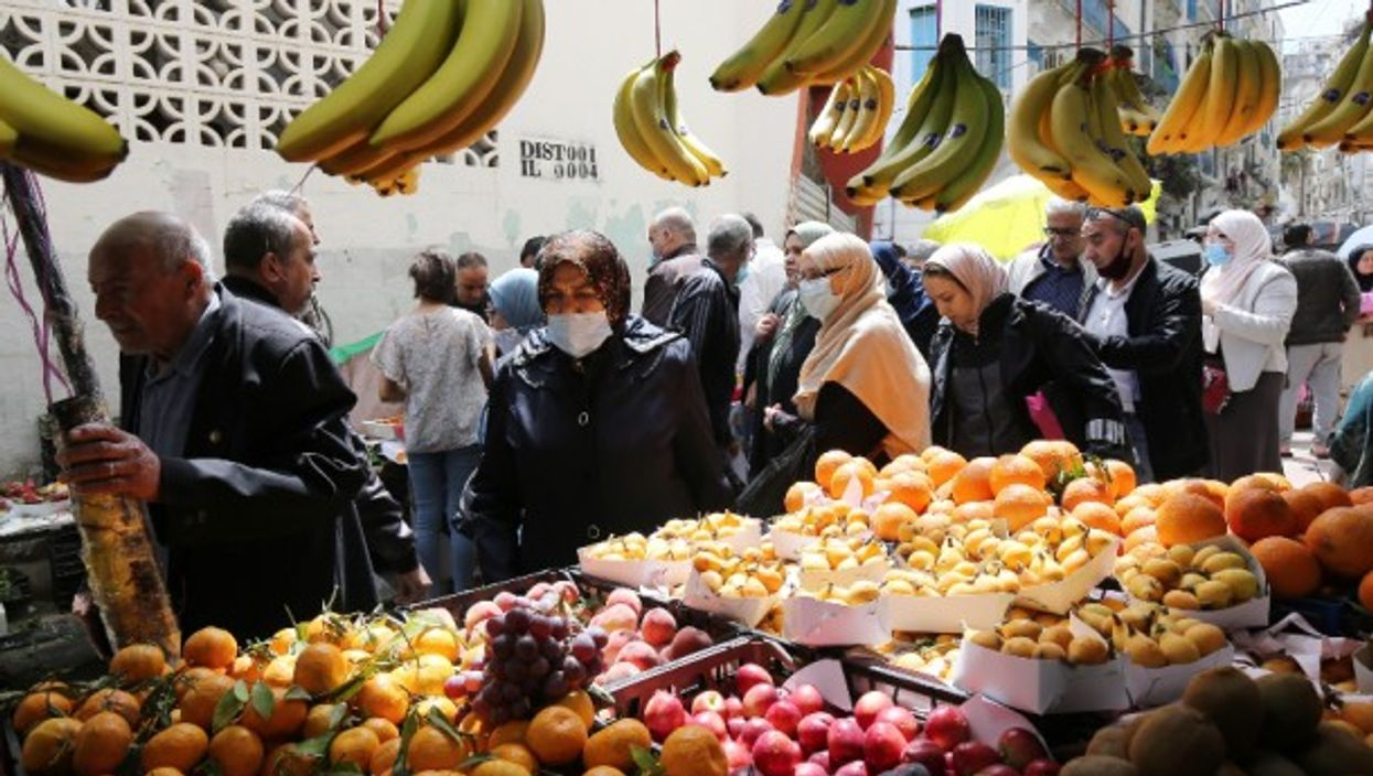 People buying food in a market on the first day of the month of Ramadan in Algiers