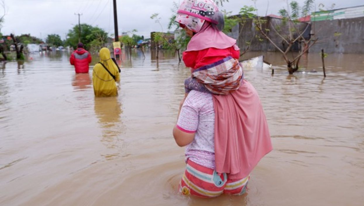 People flee their homes in Makassar City, eastern Indonesia, where heavy rains have caused massive floods during monsoon season.