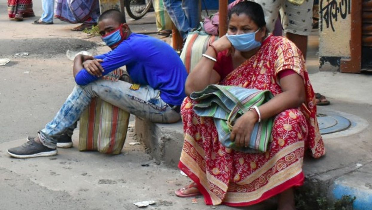 People in India wait for rice rations.