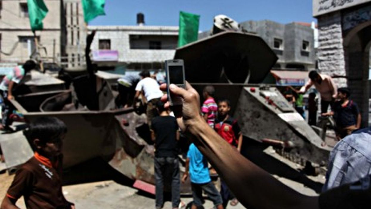 People on the remains of a destroyed Israeli military vehicle in the Gaza Strip