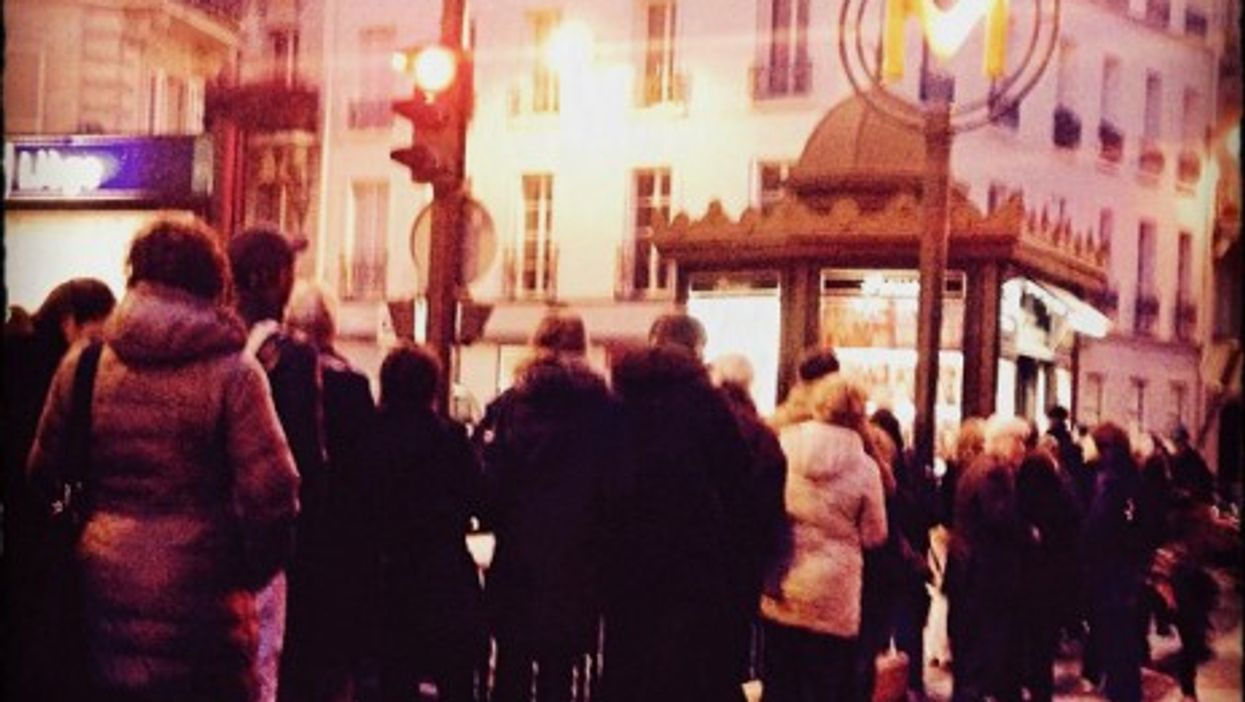People queuing outside a newsstand in Paris