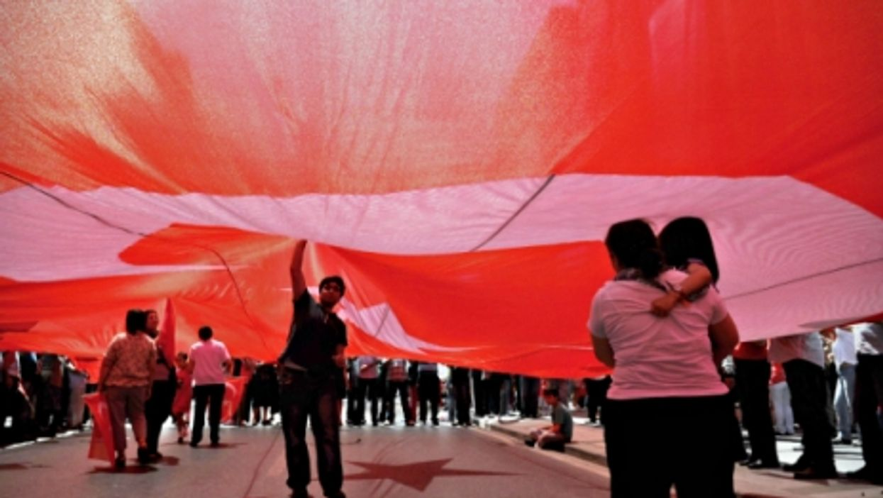 People under a giant Turkish flag in Istanbul