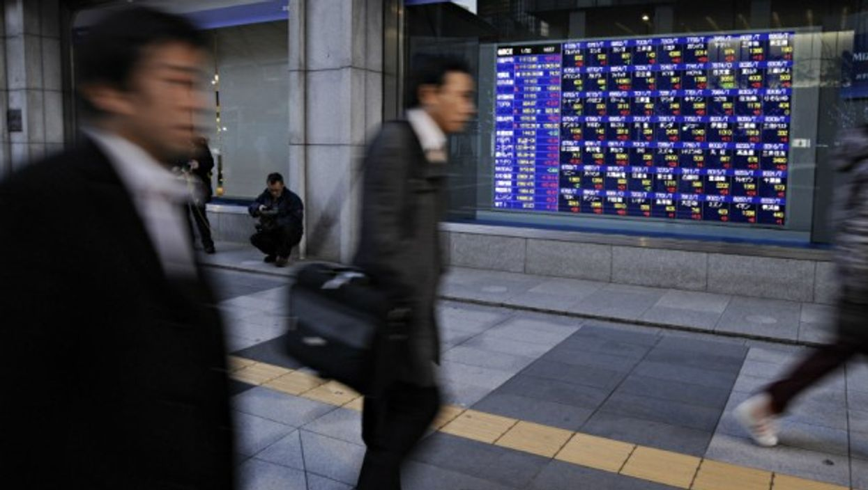 People walking by an electronic board showing stock indexes on Jan. 30, 2013 in Tokyo, Japan