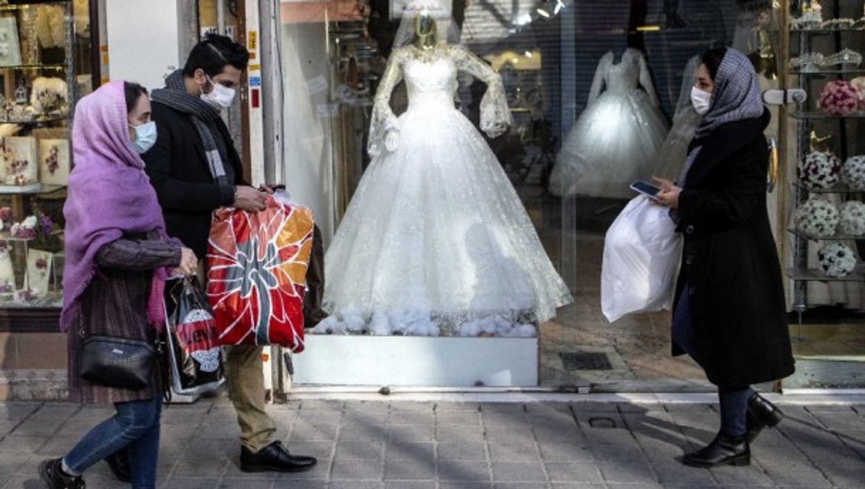 People walking past a closed wedding dress store in Tehran, Iran