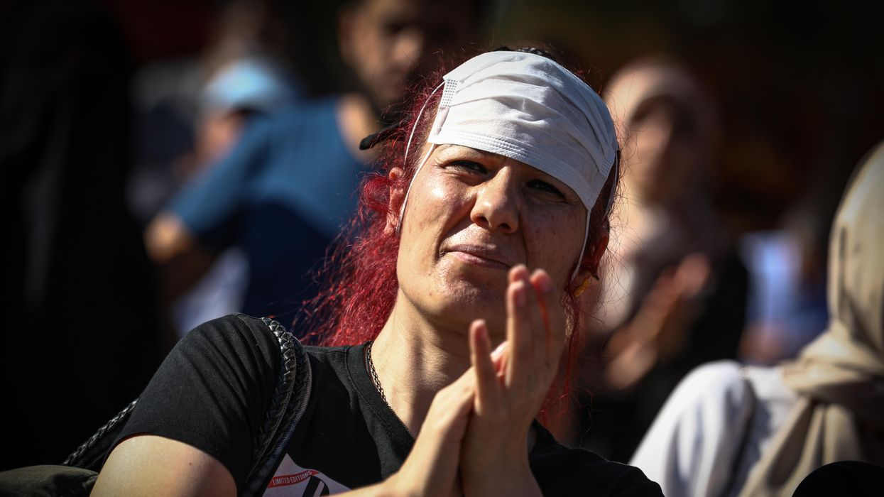 photo of a woman with a covid mask on her forehead clapping at an anti-vaccination protest in Ankara, Turkey