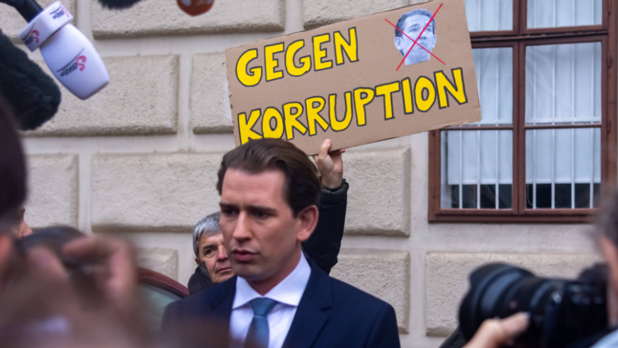 """Photo of former Austrian Chancellor Sebastian Kurz in front of a protestor holding a placard that read """"Against corruption"""" in Austrian"""
