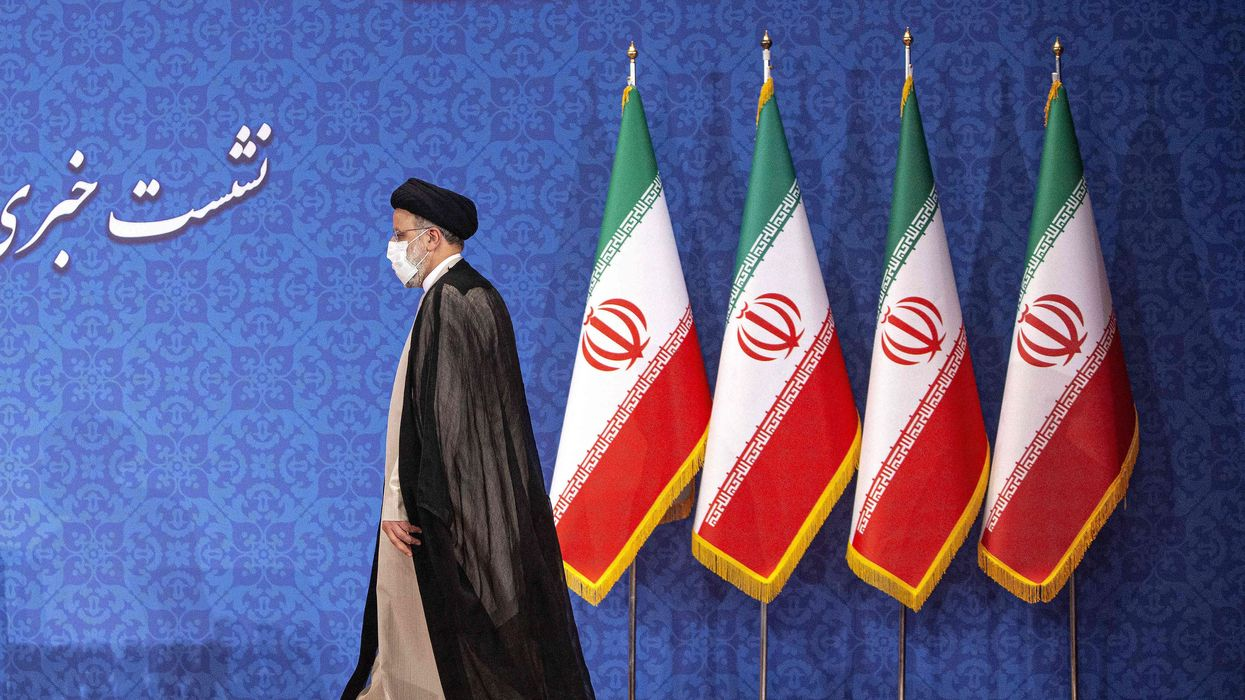 Photo of Iran's President Ebrahim Raisi walking on a stage in front of Iranian flags