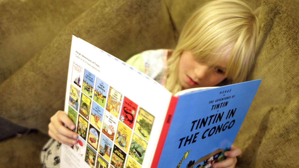 Photo of little girl reading Tintin in the Congo comic book