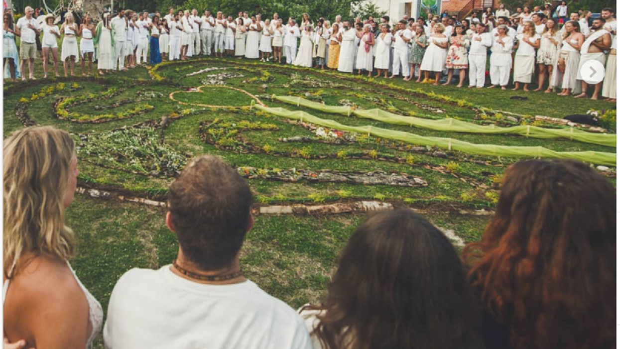 Photo of people dressed in white standing in a circle with arms interlocked