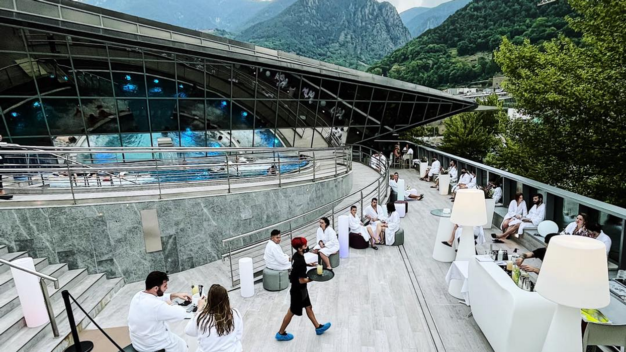 Photo of people enjoying Andorra's Caldea spa, with mountains in the background