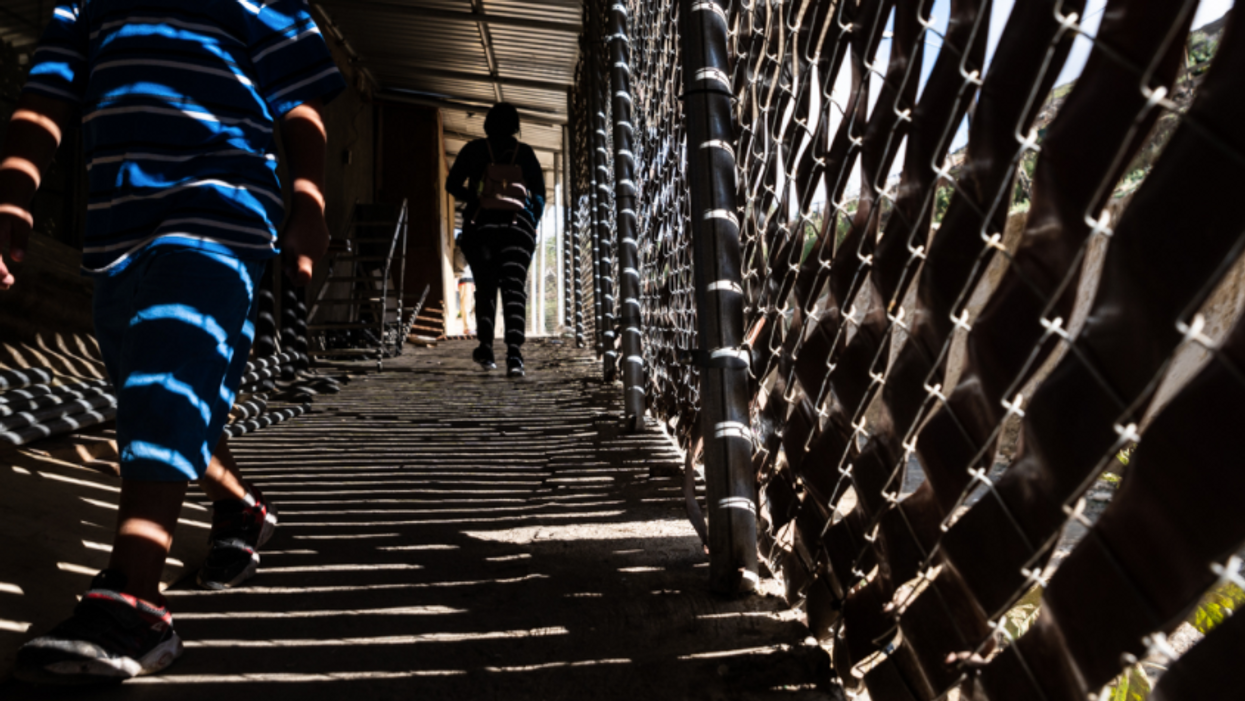 Photo of people walking alongside the border between Mexico and the United States in Tijuana
