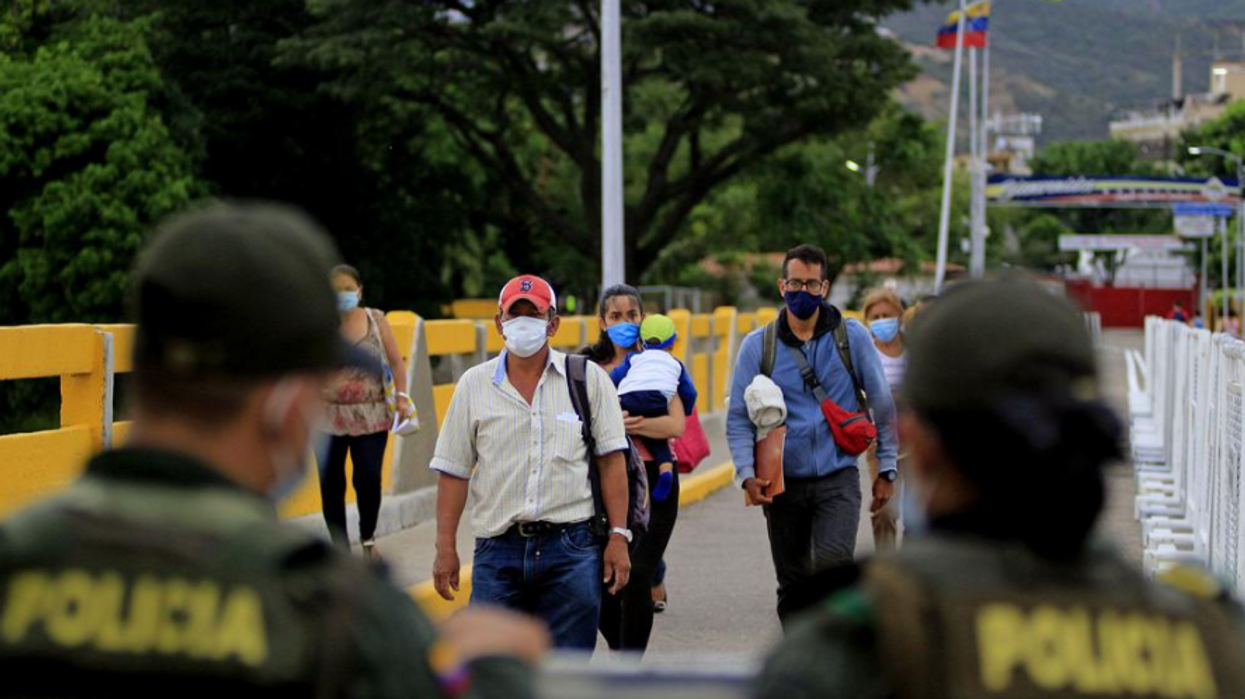 Photo of people walking toward border patrol officers as Colombia reopens its border with Venezuela after a 14-month closure to curb the spread of COVID-19.