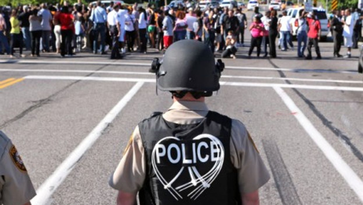 Police await protesters in Ferguson on Aug. 13.
