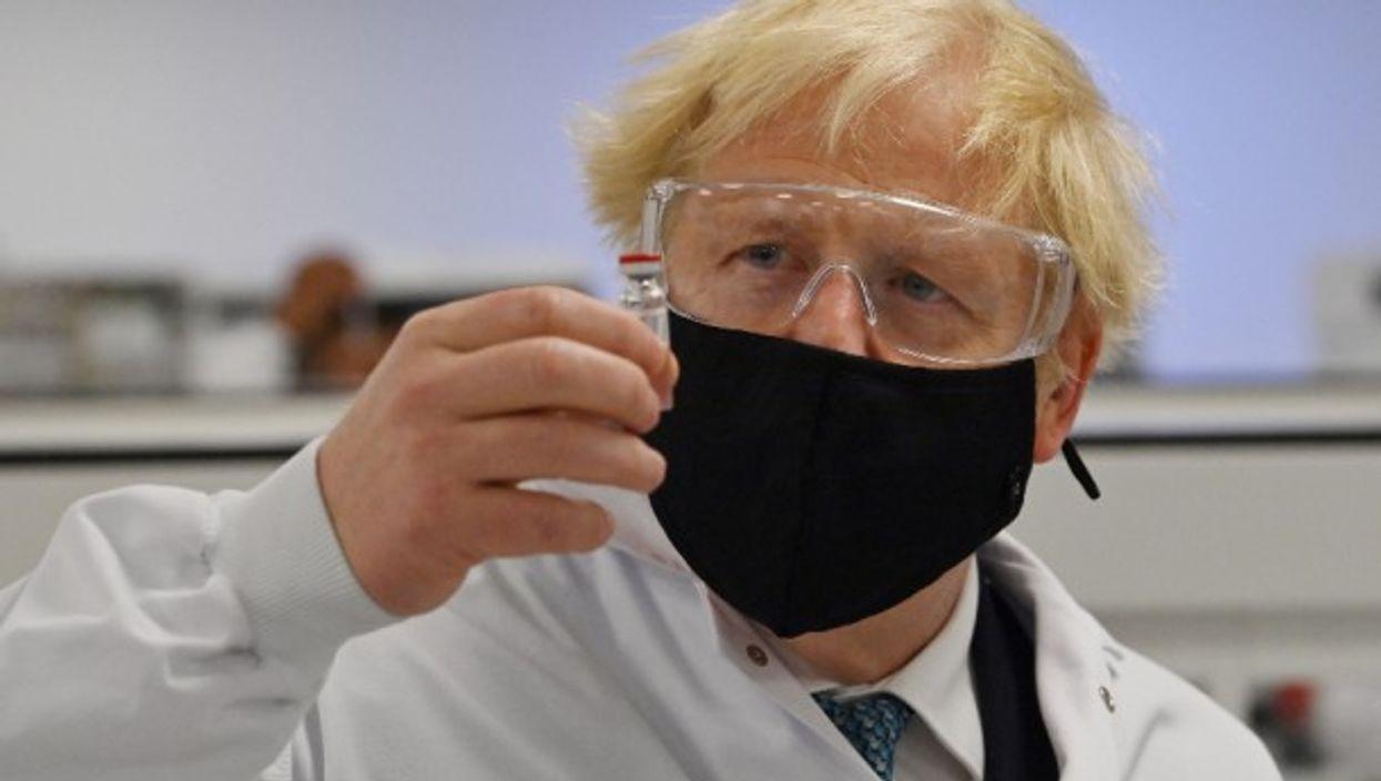 Prime Minister Boris Johnson holds a vial of the Oxford/AstraZeneca vaccine Covid-19 candidate vaccine