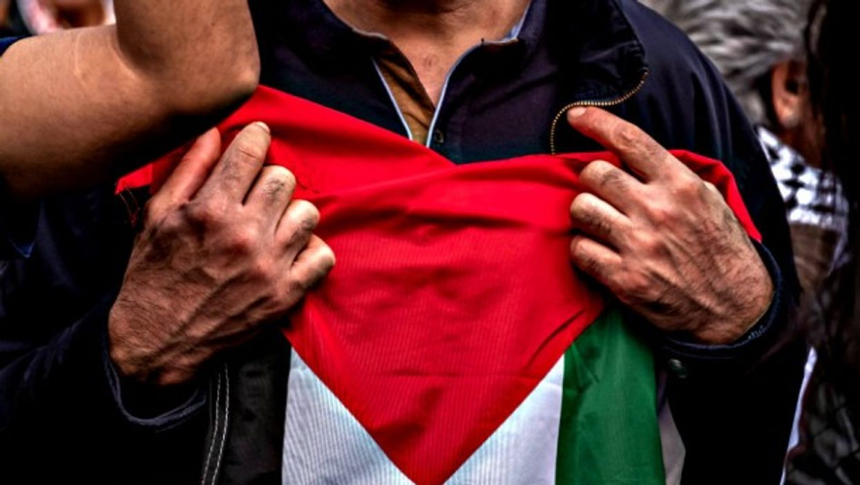 Protester holding a Palestinian flag to his chest