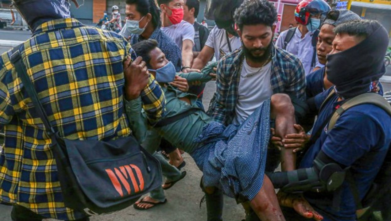 Protesters carry a wounded man after police and military opened fire on the crowd, killing 18, during the military coup demonstrations in Yangon, Myanmar.
