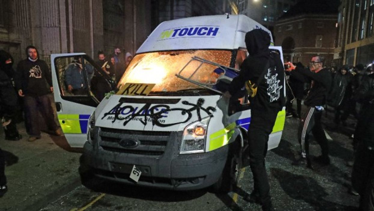 """Protesters destroy a police van in Bristol during a """"Kill the Bill"""" demonstration against a controversial new anti-crime bill."""