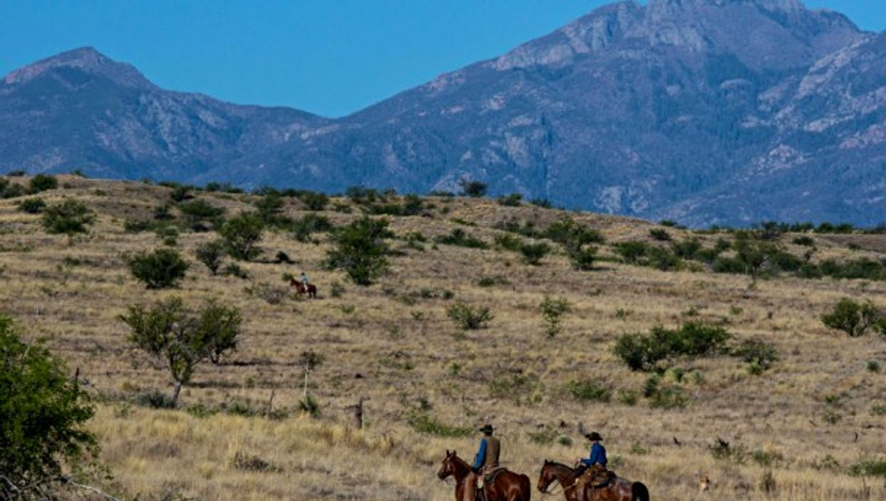Ranchers ride horses on the outskirts of the arid Tucson