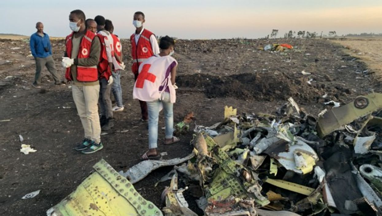 Rescuers work beside the wreckage of an Ethiopian Airlines' aircraft at the crash site