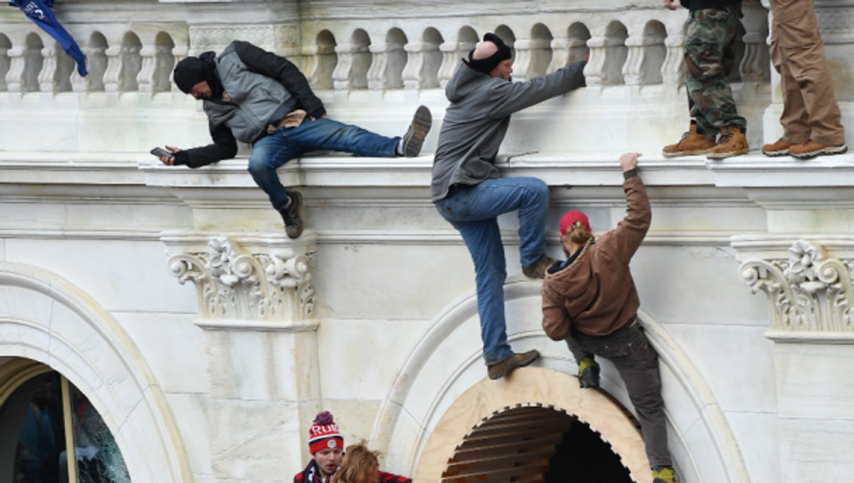Rioters climb the wall of the U.S. Capitol in Washington, D.C. on Wednesday.