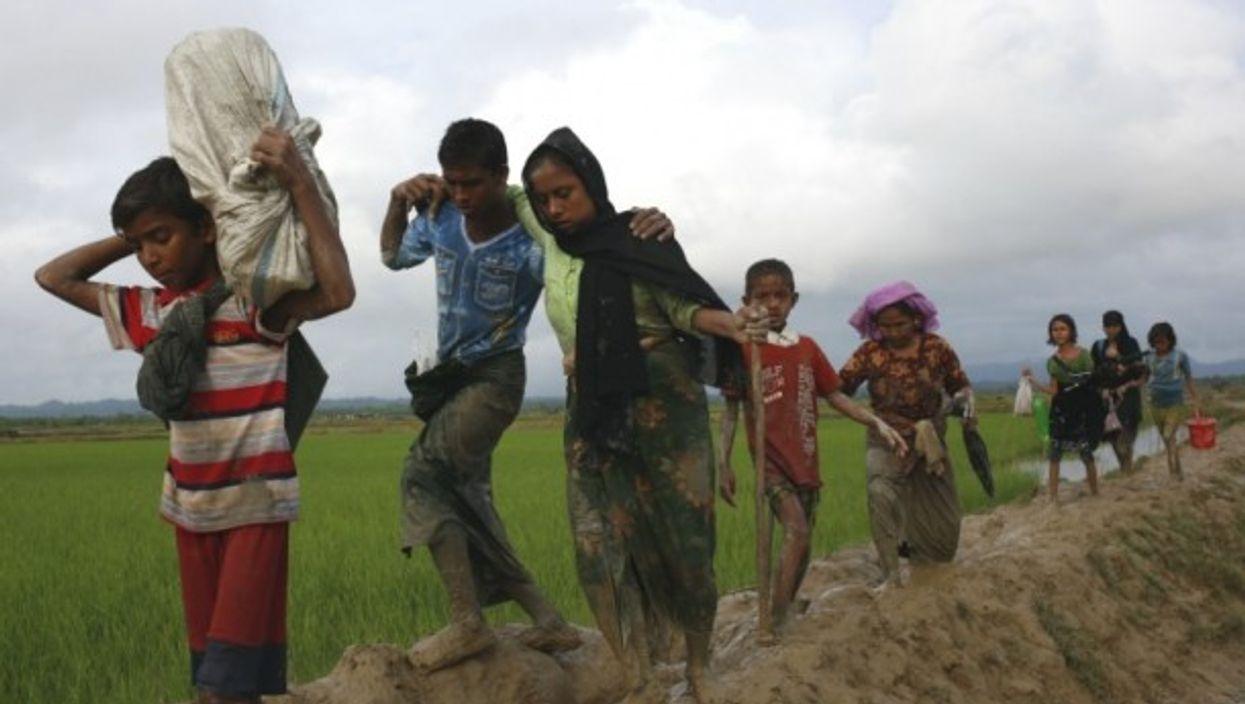 Rohingya refugees walk through the mud