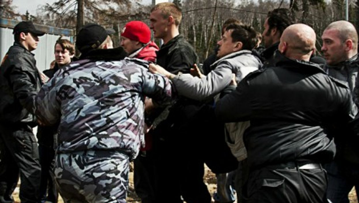 Russian environmentalists trying to break through a cordon of security guards