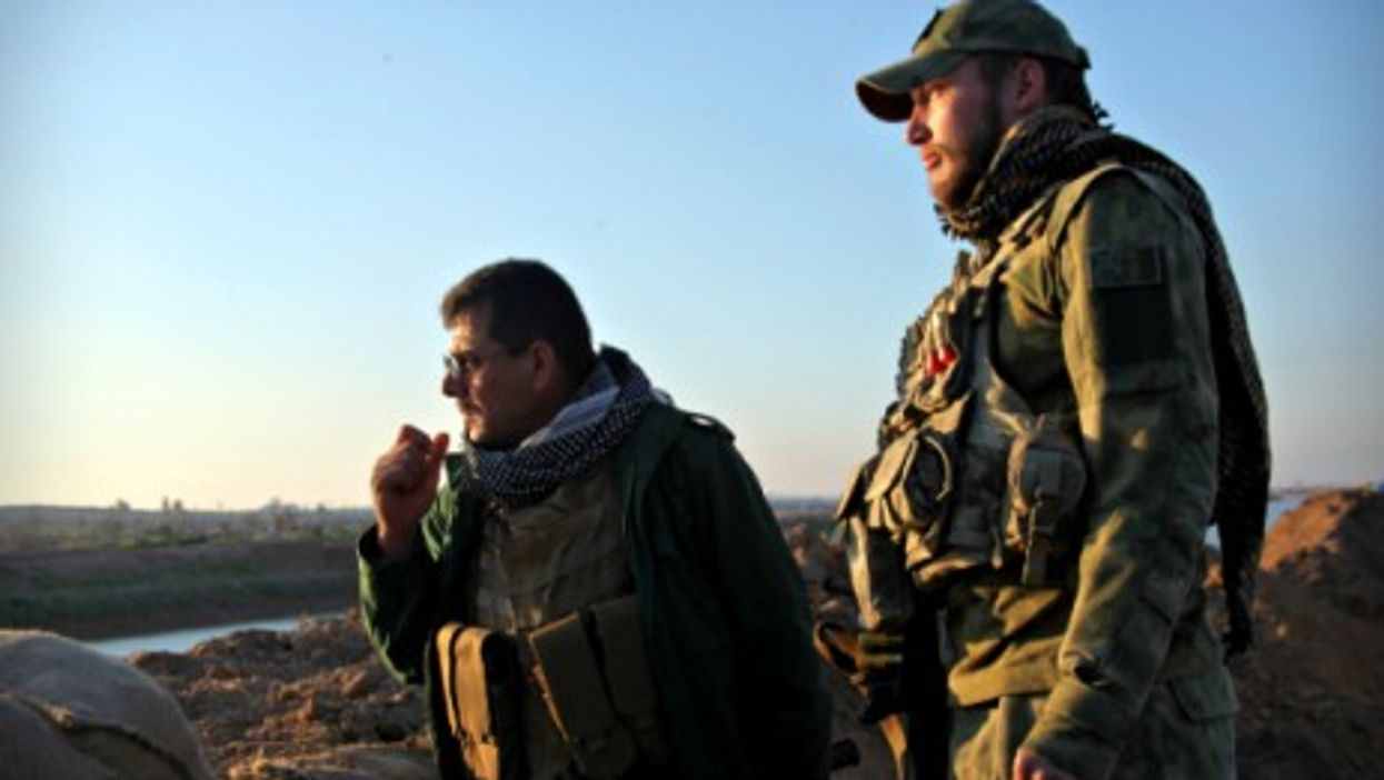 Shia soldiers look over an ISIS-controlled area near Kirkuk, Iraq