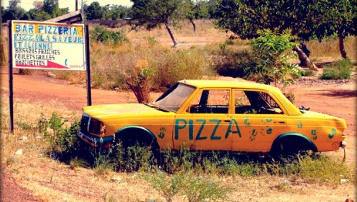 Signs for a pizzeria, a few miles from Burkina Faso's capital, Ouagadougou