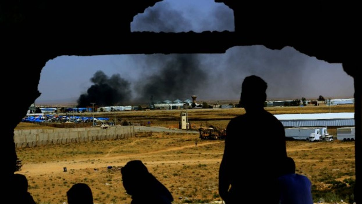 Smoke rises from the Syrian side at the Nasib Border Crossing between Jordan and Syria.