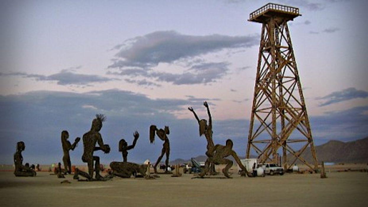Statues of people kneeling before an oil derrick