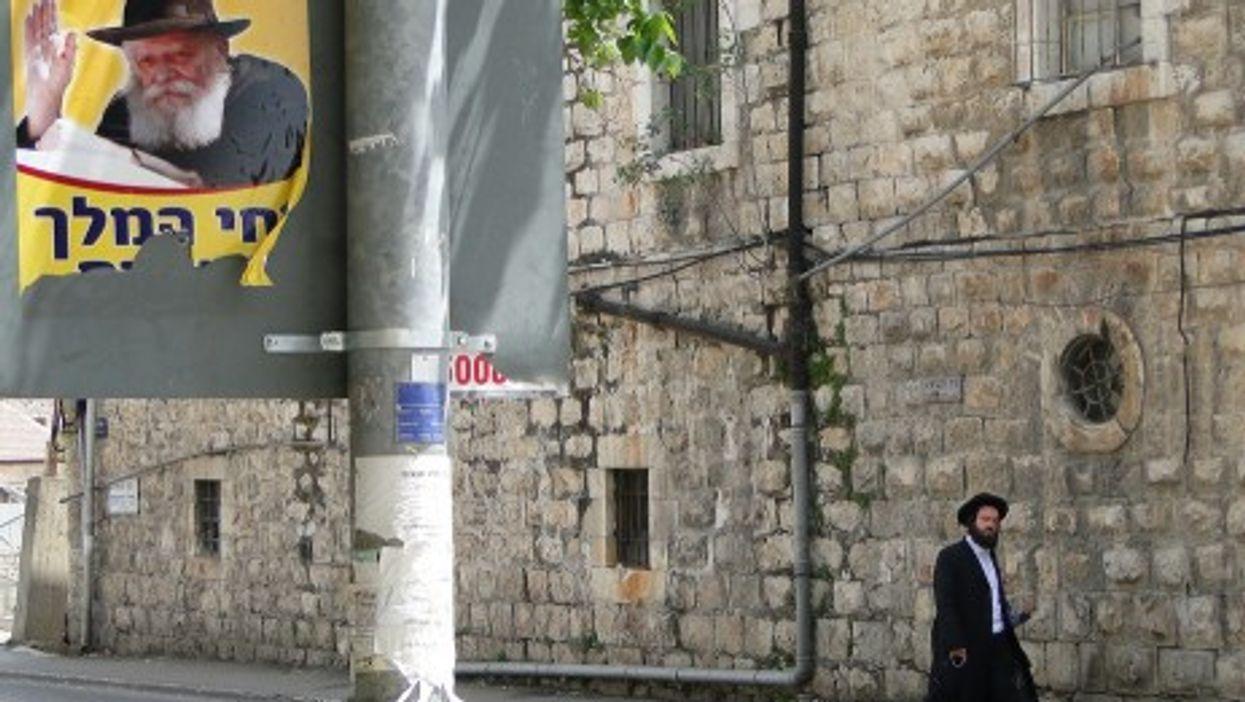 Street poster of Lubavitcher Rebbe, Rabbi Menachem Mendel Schneerson, with Orthodox pedestrian