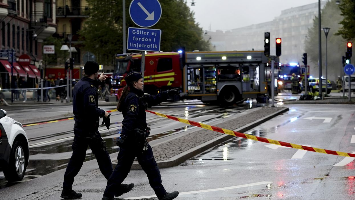 Swedish police officers walk towards a cordoned-off scene in Gothenburg, after the Sept. 28 explosion at a multi-family complex