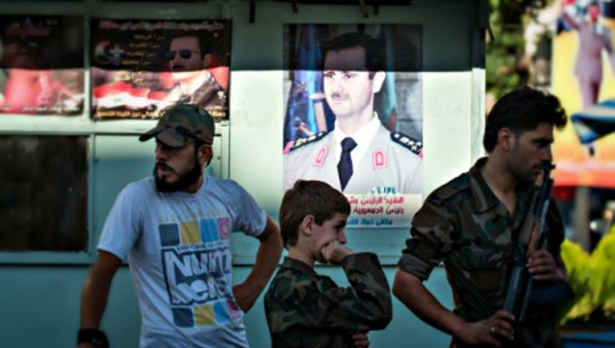 Syrian Army soldiers at a chekpoint in Damascus in June