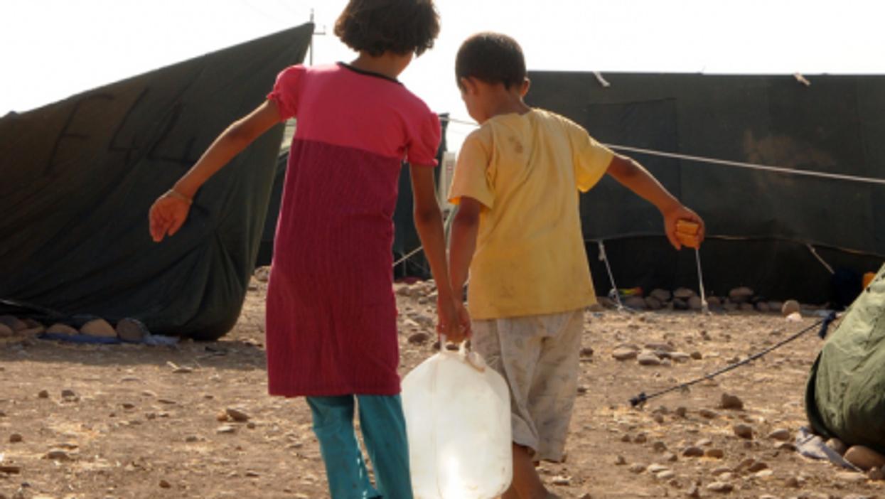 Syrian children fetch water at Kawergost Refugee Camp, some 50 km north of Erbil, capital of Iraq's autonomous Kurdish region.