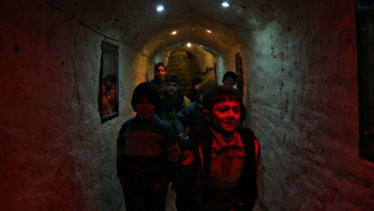 Syrian children that live in underground to escape the threat of airstrikes and mortar attacks.