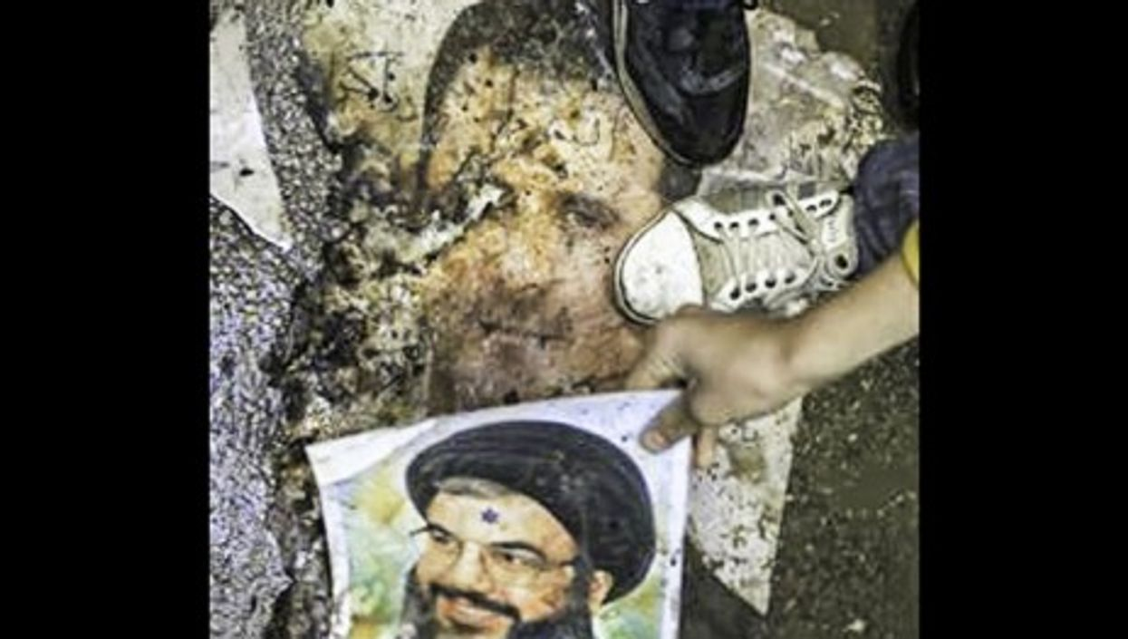 Syrian protesters step on posters of Bashar al-Assad and Hezbollah leader Hassan Nasrallah in January 2012 (FreedomHouse2)