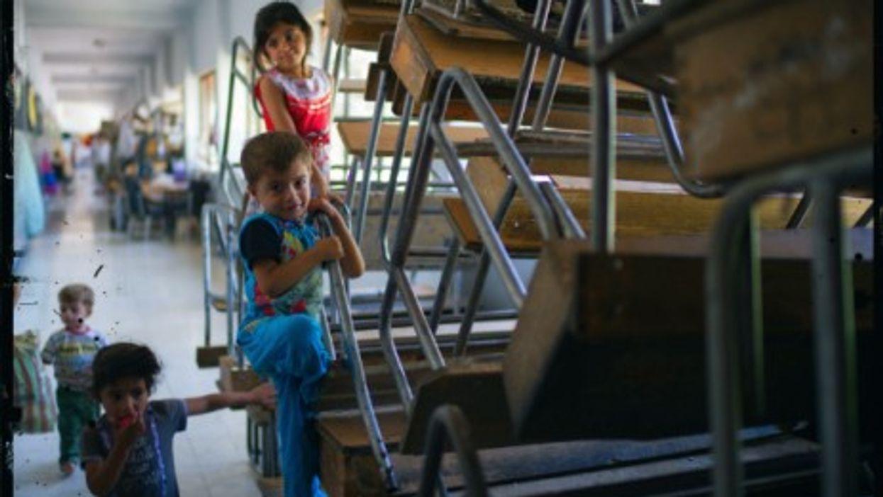 Syrian refugee children play in a school in Damascus