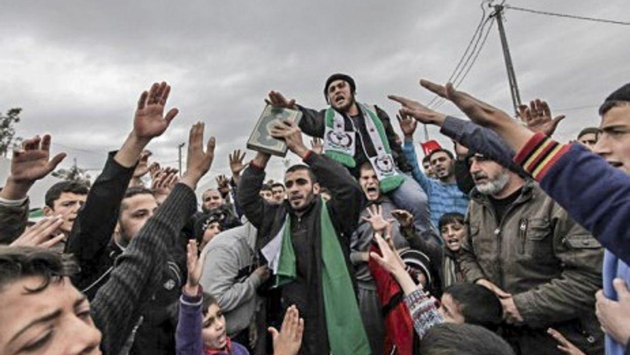 Syrian refugees center around a Koran