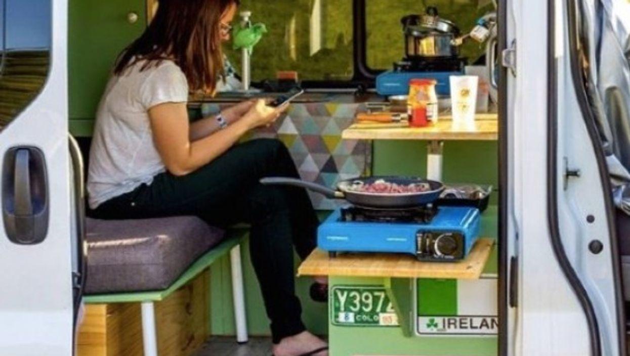 The author having dinner inside her camper van.
