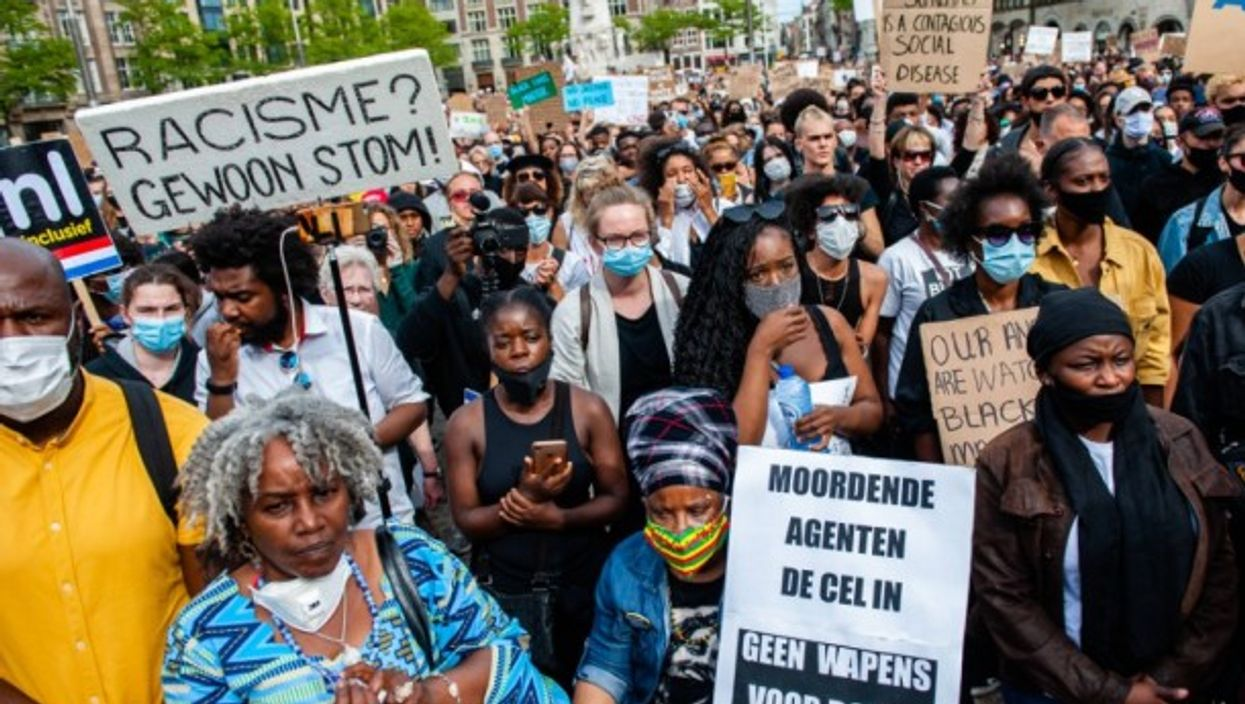 Thousands protesters are seen holding placards while listening to the speeches at the Dutch protest at Dam Square.