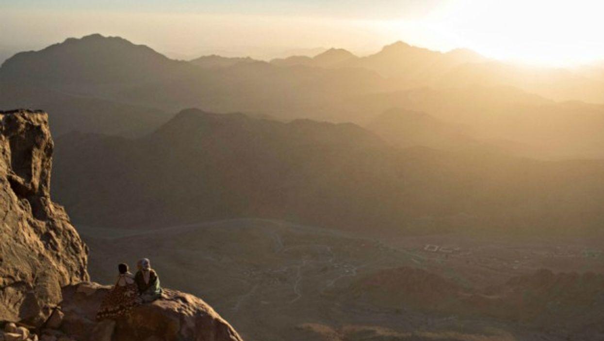 Tourists watch the sunrise on Mt. Sinai
