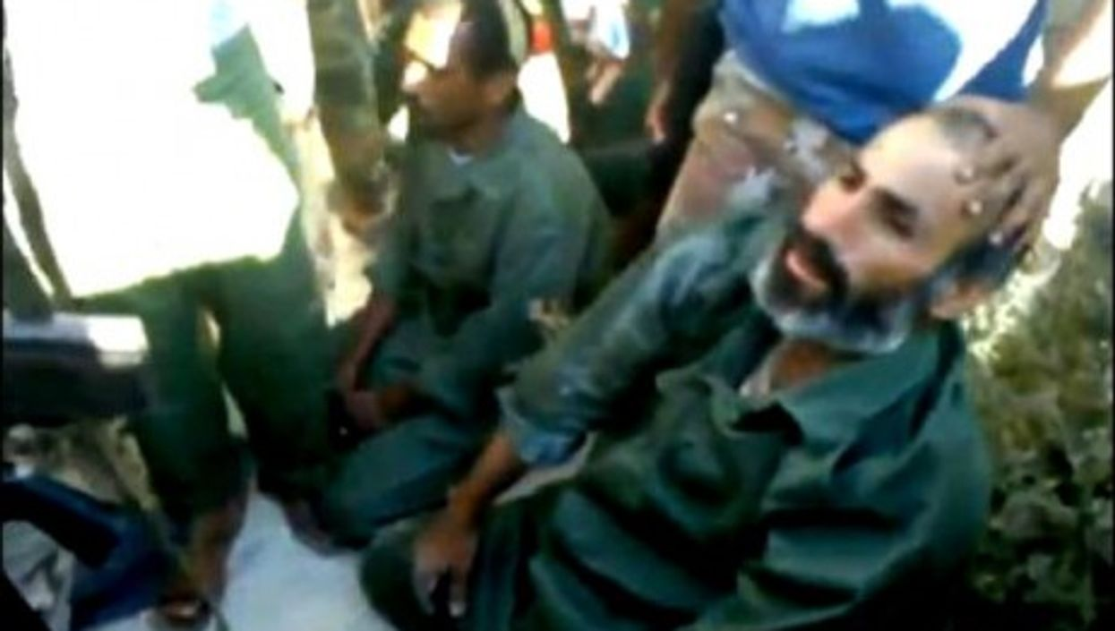 Two accused mercenaries being captured and questionned