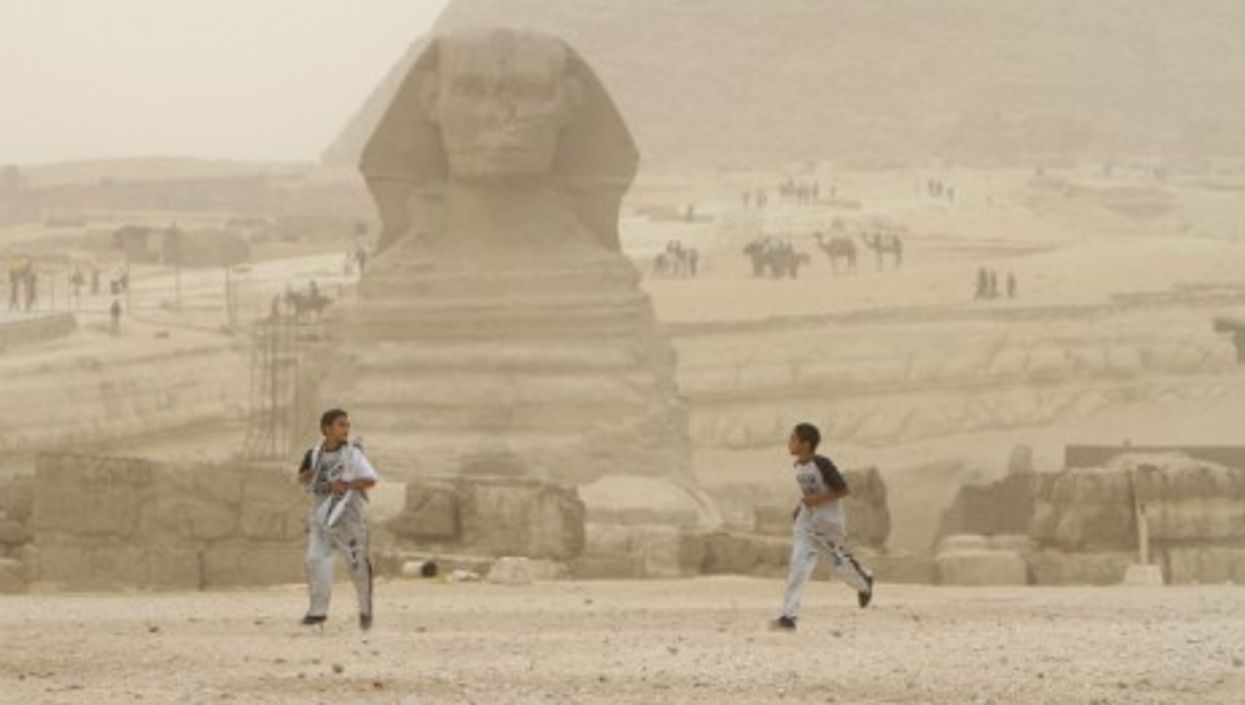 Two boys run in front of the great sphinx of Giza