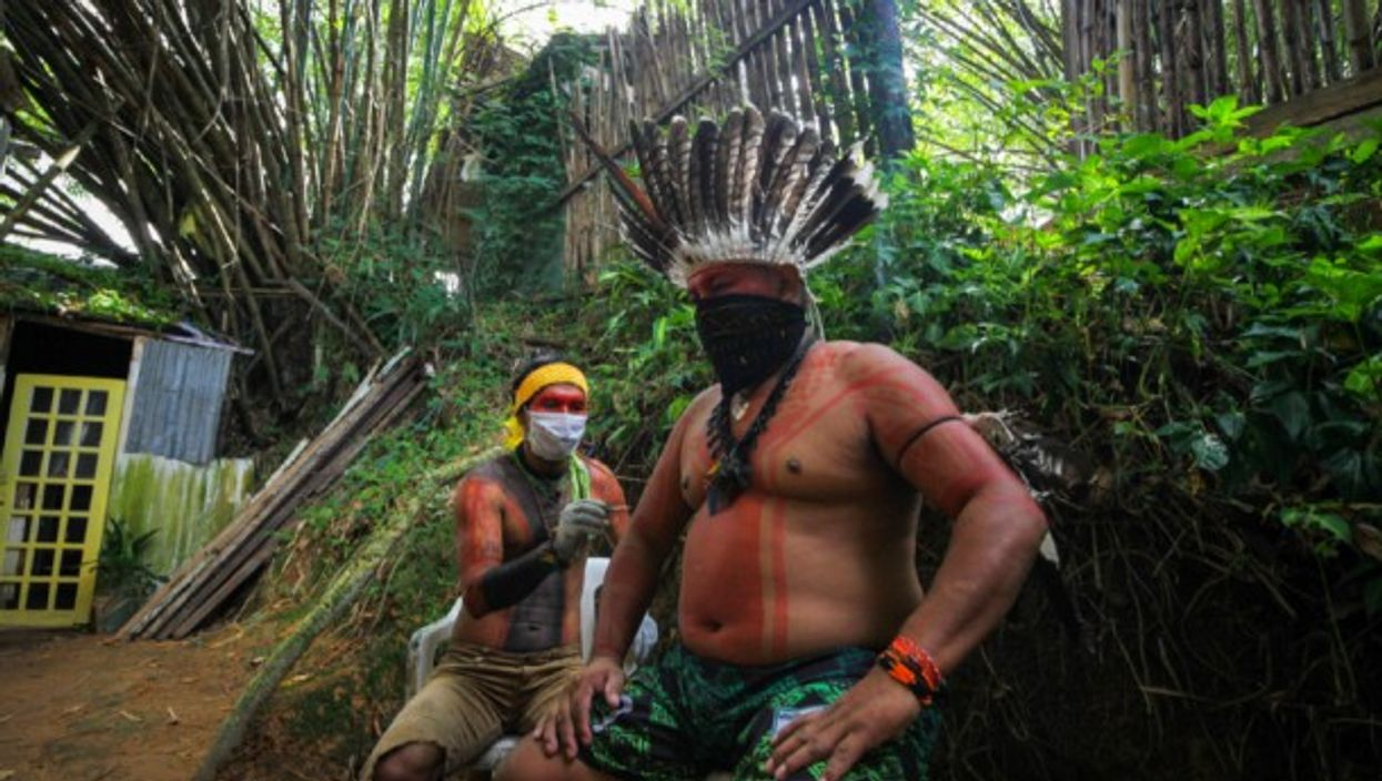 Two men of an indigenous family seen wearing face masks for protection against the coronavirus in Manaus, Brazil.