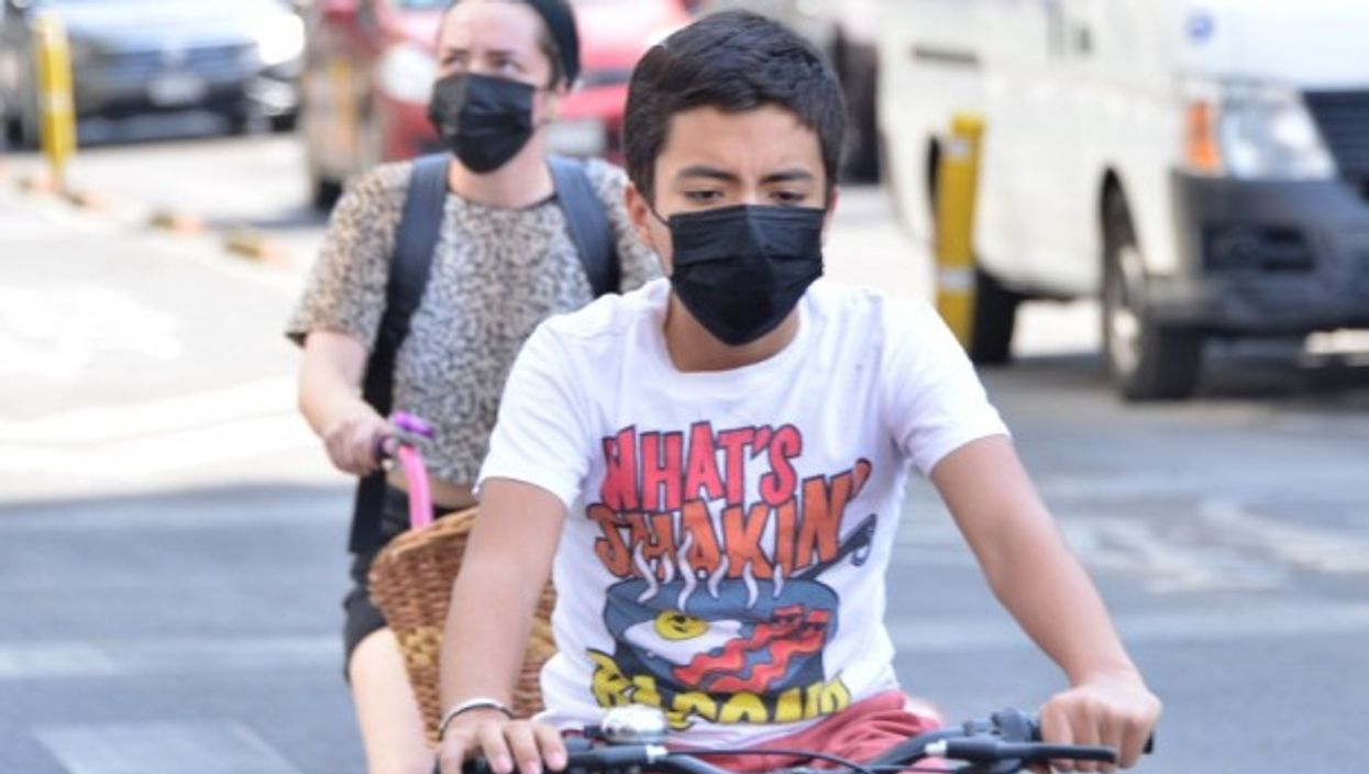 Two young ride a bike wearing protective face masks.