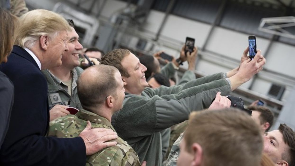 U.S. President Donald Trump takes selfies with U.S. service members during stop-over at Ramstein Air Force Base in Germany.